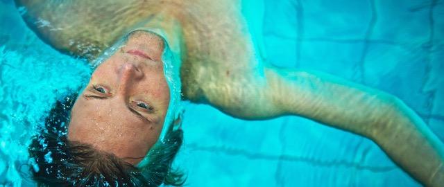Georg Pelzers Spielfilmdebüt Fluten | Das Bild zeig einen jungen Mann der auf dem Rücken an der Wasseroberfläche eines Schwimmbeckens treibt. Sein Blick ist müde.
