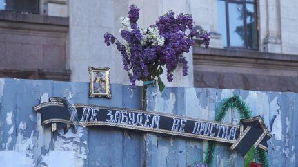 Das Bild zeigt einen lila-weißen Fliederstrauß, der an einem Mauerpfosten befestigt ist. Darunter hängt an er Mauer ein Trauerbanner in russischer Schrift. Links neben dem Strauß ein gerahmtes Marien-Bildnis.