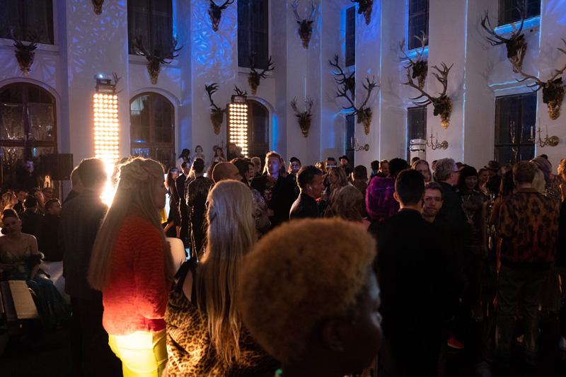 Der Festsaal des von Schloss Moritzburg gefüllt mit einer Menge von Statisten, die eine Partyszene spielen.