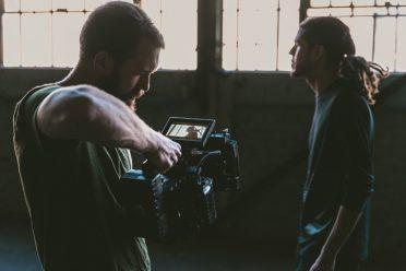 Ein Mann filmt einen anderen jungen Mann im Profil.