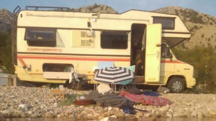Wohnwagen mit geöffneter Tür an einem See. Vor dem Wohnmobil an steinigen Ufer ein Sonnenschirm, Decken, Kissen und eine Gitarre.