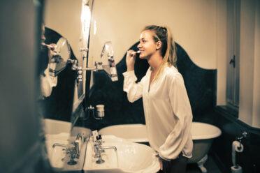 Eine blonde Frau putzt sich im Bad vor dem Spiegel die Zähne. Der Wasserhahn läuft.